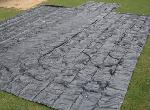 Black Lumber Tarp Spread Out on Lawn
